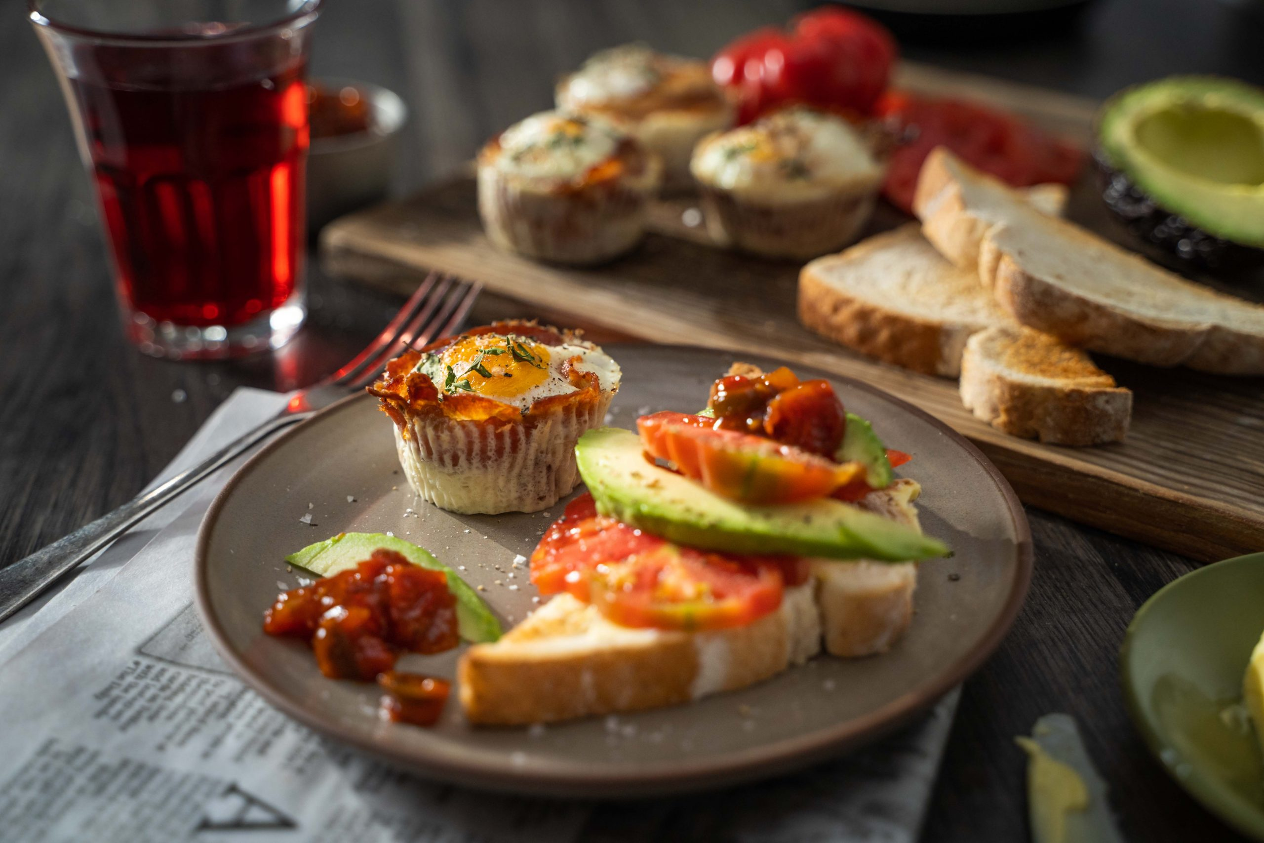 Bacon & egg cups with tomato and avocado toast on a plate with relish and a glass of juice.