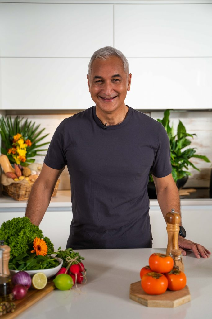 Mike McRoberts standing in a white kitchen surrounded by an assortment of fruit and veggies in baskets or on wooden boards.