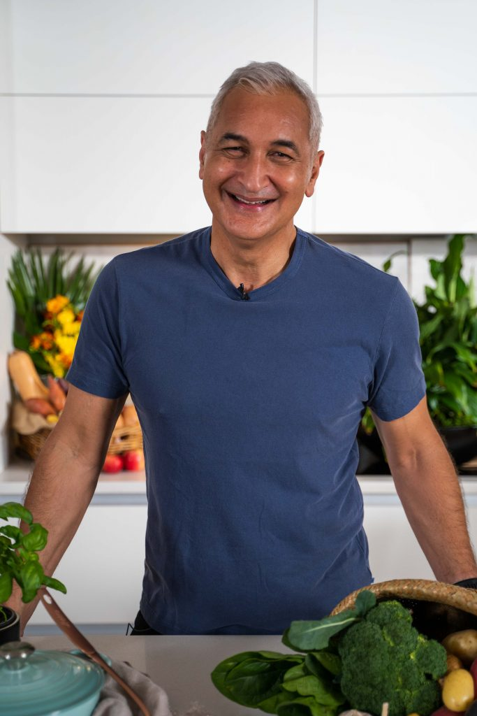 Mike McRoberts standing in a white kitchen in a blue T-Shirt surrounded by fruit and vegetables