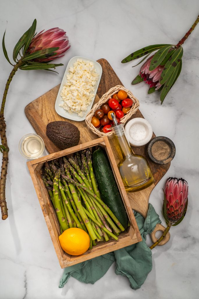 Asparagus, lemon and cucumber in a crate, avocaod, tomatoes, cheese, oil, salt & pepper on wooden board