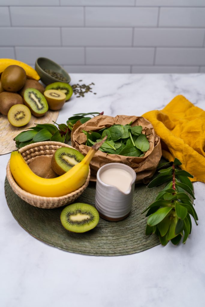 Whole and halved kiwifruit, bananas, spinach in a paper bag and milk in a jug on a green placemat with greenery and yellow tea towel