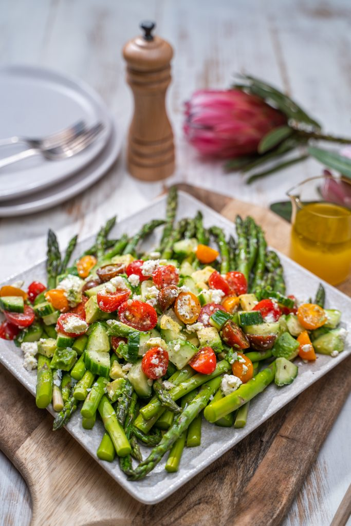 Asparagus on a plate topped with chopped avocado and tomatoes surrounded by plates and forks, a flower and a salt grinder on a wooden board
