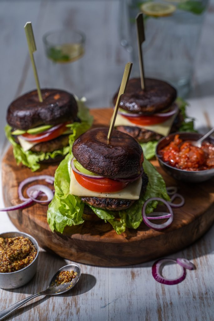 3 lettuce, meat, cheese, tomato and red onion burgers with mushroom buns on a wooden board with mustard and salsa in small bowls