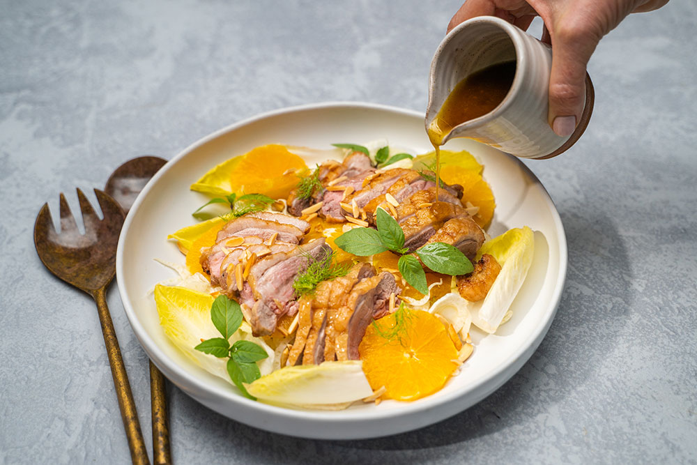 Crispy duck breast slices on a chicory, orange and Thai basil salad with Lee Kum Kee dressing pouring shot