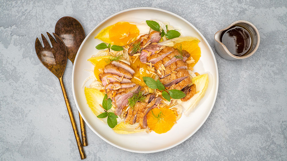 Crispy duck breast slices on a chicory, orange and Thai basil salad with Lee Kum Kee dressing