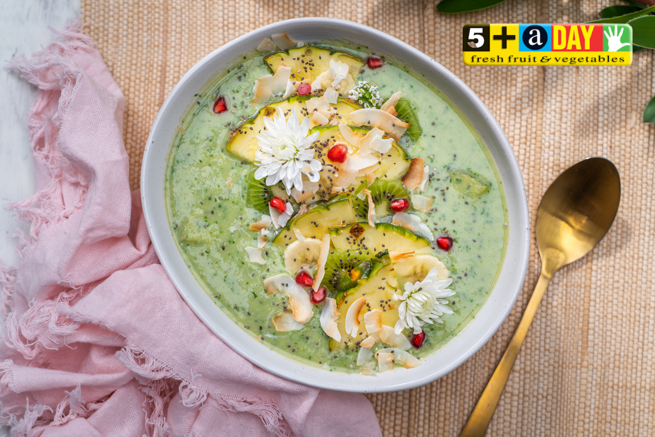 Kiwifruit and spinach smoothie topped with pineapple, kiwifruit, coconut and flowers in a bowl with golden spoon and pink cloth