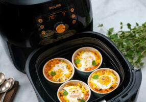 Four Mac and cheese and half baked egg ramekins with oregano leaves cooked in a Philips Premium Airfryer